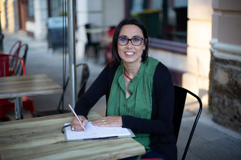 Image is of author Nadia L King sitting at an outdoor cafe table. There is a pad of paper on the table. She is holiding a pen and looking a the camera,