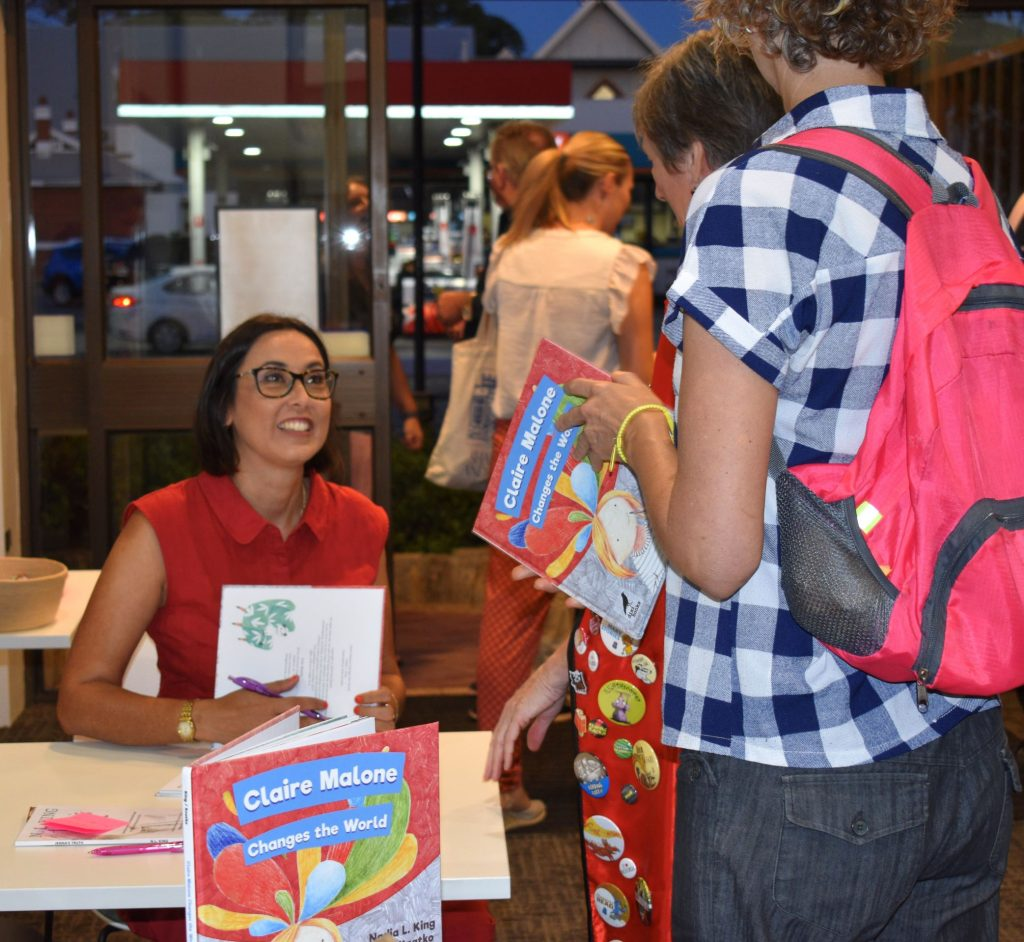 Author Nadia L King signing copies of her book and talking to readers