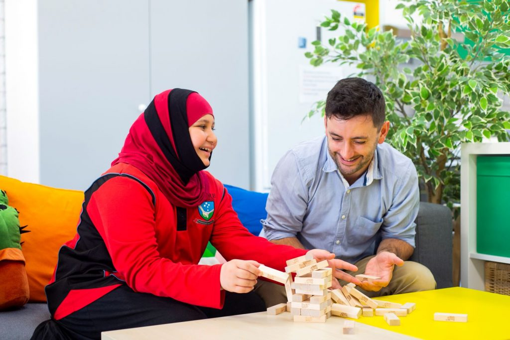 a female student wearing a head scarf and a male mentor laughing while playing jenga