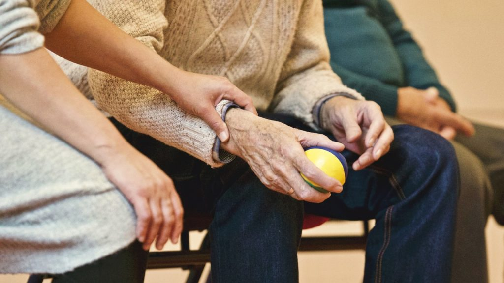 Image: two people, one old and one young, seated on a chair. We only see the bottom half of them, the emphasis being on their hands. The younger person rests her hand on her elder's arm.
