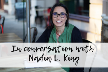 Image of Nadia L King sitting at a outdoor cafe table. Overlaying the image are the words In conversation with Nadia L. King