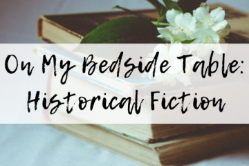 """ID: a stack of old books with a white flower sitting on the top. Overlaid is the title of the blog post: """"On My Bedside Table Historical Fiction""""."""