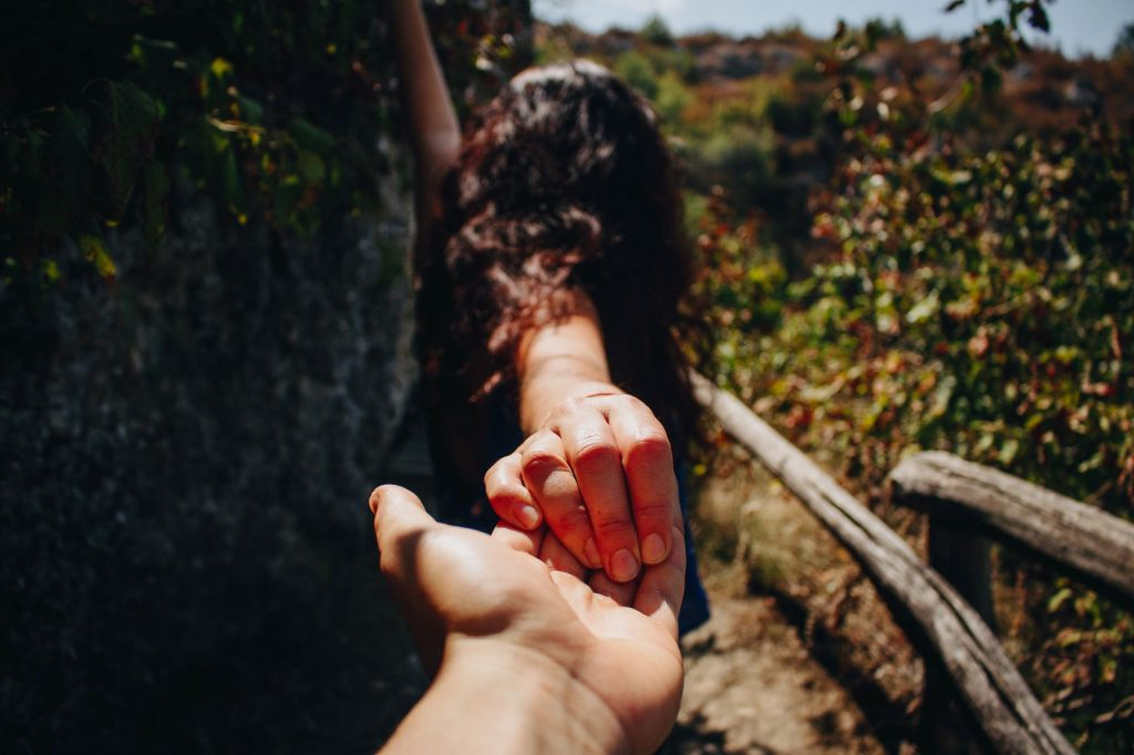 Image: a girl with one arm stretched out to touch the side of a cliff and her other hand reaching out to grab someone's hand