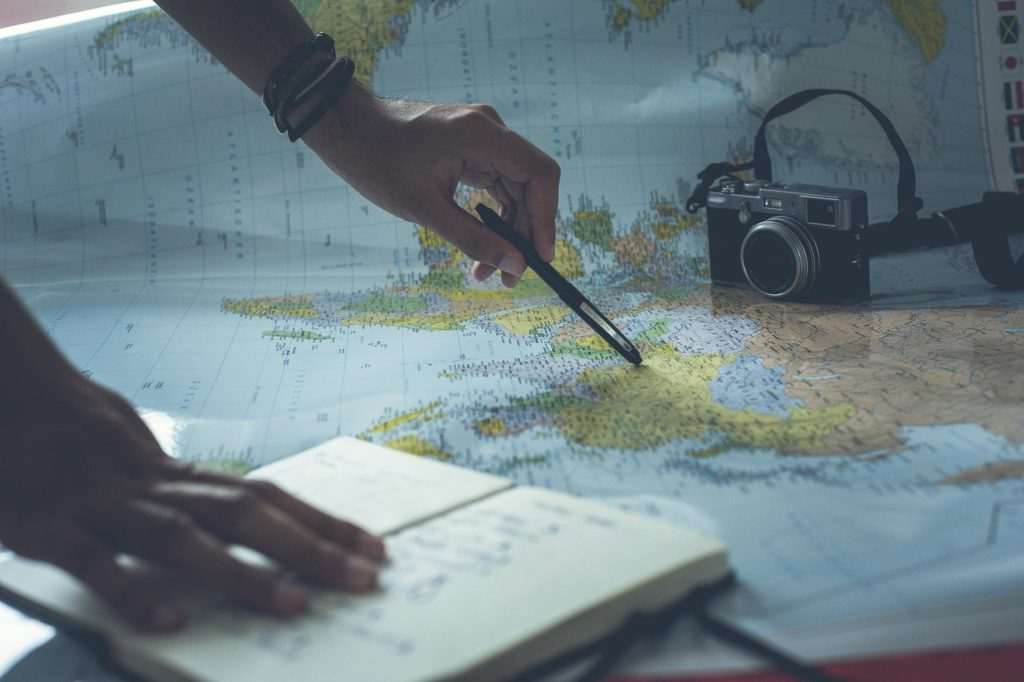 Image is of a world map laid out with a camera and notebook sitting on top. A person's arm is reaching out with a pen towards the map.