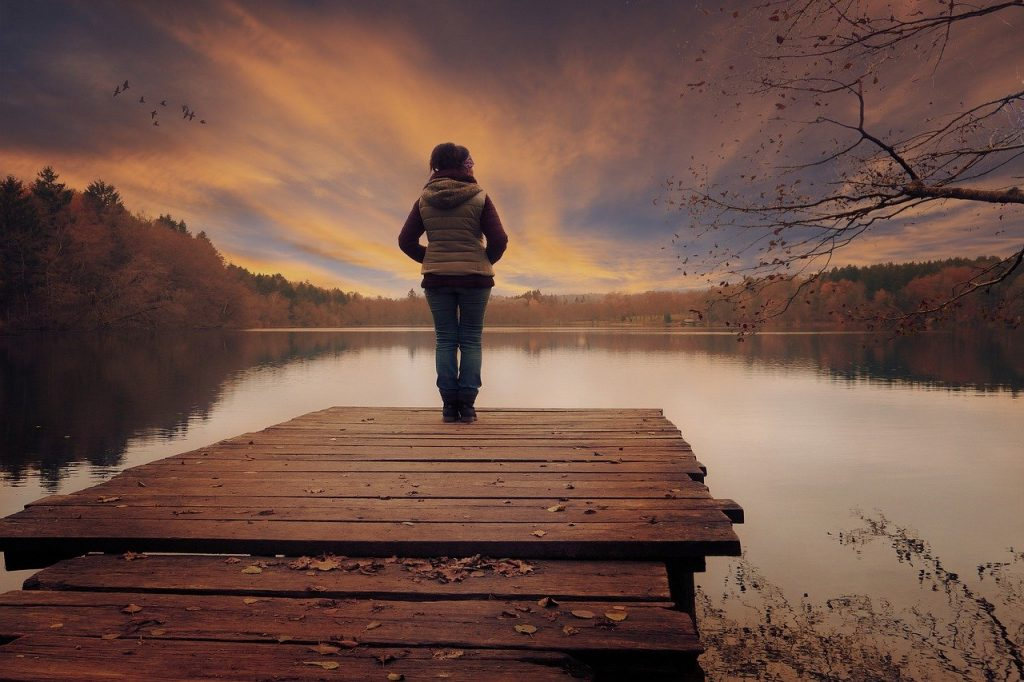 Image is of a person standing on a wooden jetty looking out over a lake at sunset